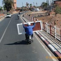 Auf den Straßen von Marokko. Eine Person fährt das Moped und der Mitfahrer hält eine Tür, die so transportiert wurde.