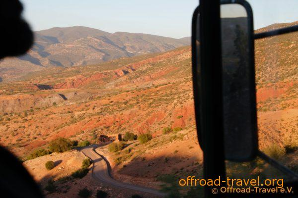 Mit Blick aus dem Fenster des Magirus sieht man herrliche Landschaft mit orangefarbener Erde und grünen Bergen. In mitten der Landschaft sieht man eine Straße.